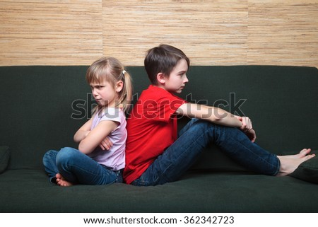 Brother and sister  wearing casual clothes  sitting on a green sofa back to back sad and frown - stock photo