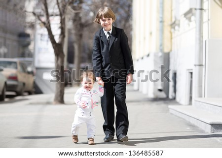 Brother and sister wearing formal clothes walking on a sunny street - stock photo