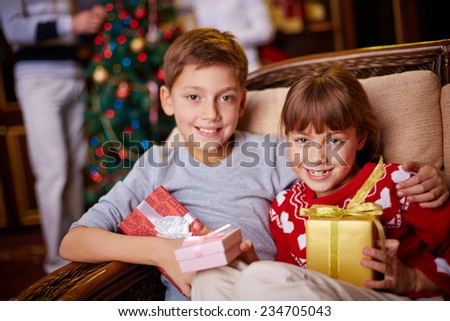 Brother and sister with Christmas gifts looking at camera - stock photo