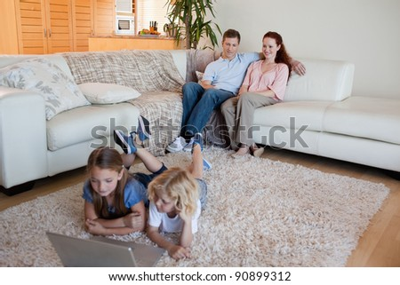 Brother and sister with laptop on the living room carpet - stock photo
