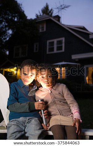 Brother and sister with torch on Halloween - stock photo