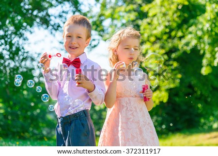 brother and sister 6 years in the park with soap bubbles - stock photo