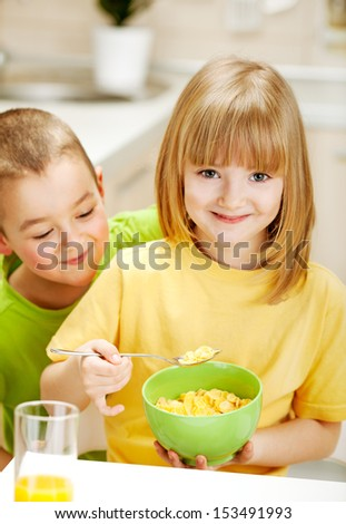 Brother peeking in his sister plate, Fun in the kitchen - stock photo