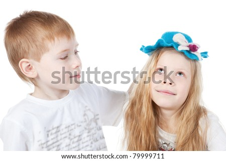 Brother puts a hat on his sister over white - stock photo