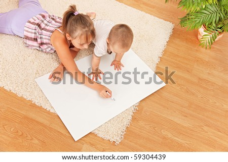 Brother watching his sister drawing on white board - stock photo