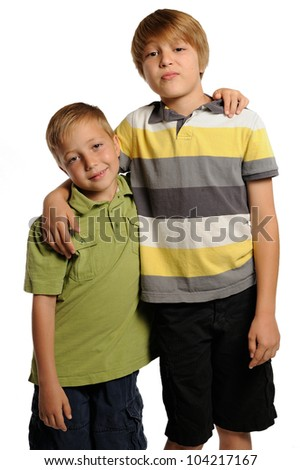 Brotherly Love. Seven and nine year old boys standing with their arms around each other. - stock photo