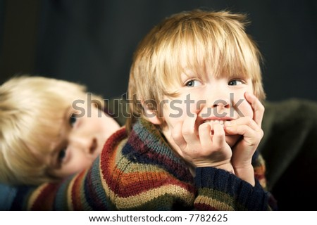 Brotherly Love, Two beautiful young boys lying down with focus on the first child, both with precious looks on their face - stock photo