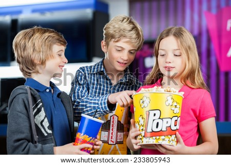 Brothers and sister holding popcorn and drinks at cinema - stock photo