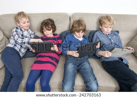 Brothers and sister using digital tablets while relaxing on sofa at home - stock photo