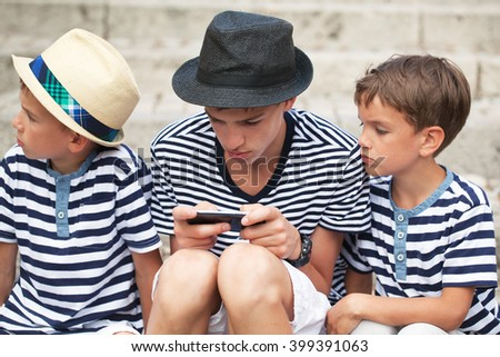 Brothers are playing game on your phone. outdoor - stock photo
