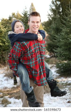 Brothers having fun at a Christmas tree farm - stock photo