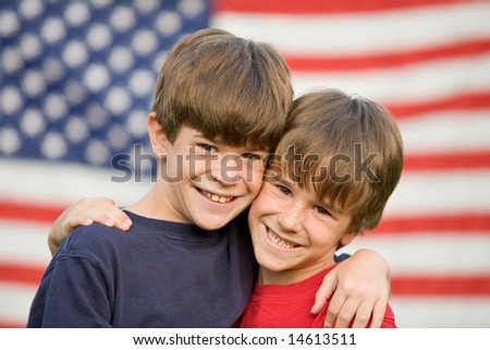 Brothers Hugging in Front of Flag - stock photo