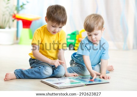 brothers kids read book together at home - stock photo