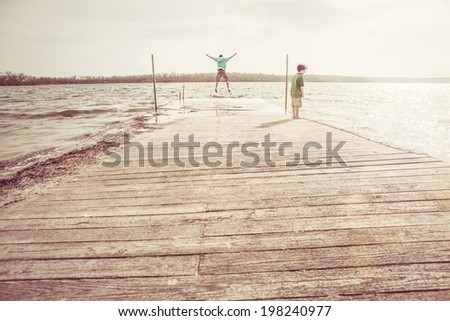 Brothers Playing on a dock - stock photo