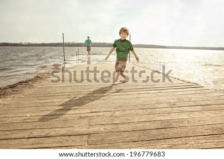 Brothers playing on a dock in the summertime - stock photo