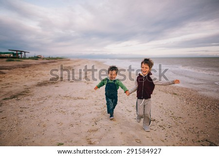 brothers running on beach holding hands smiling - stock photo