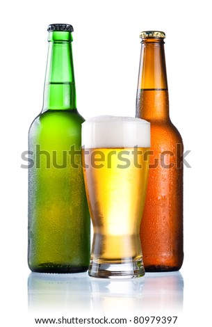 Brown and green bottles full of condensate and covered with a glass of fresh cold beer isolated on a white background - stock photo