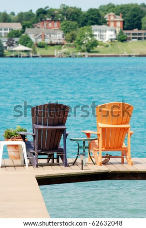 brown and orange Adirondack chairs on a dock - stock photo