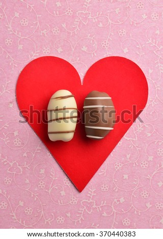 Brown and white date chocolate placed on a red color heart-shaped card. - stock photo