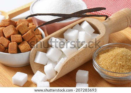 Brown and white sugar in wooden scoop and bowls - stock photo