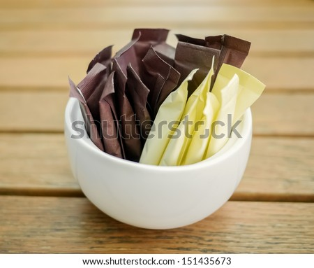 Brown and white sugar sticks on wooden background - stock photo
