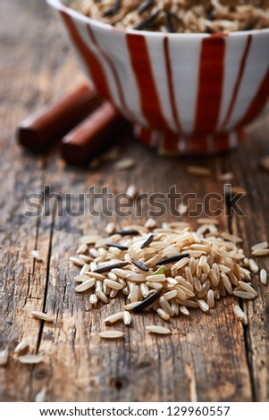 Brown and wild rice on wooden surface - stock photo