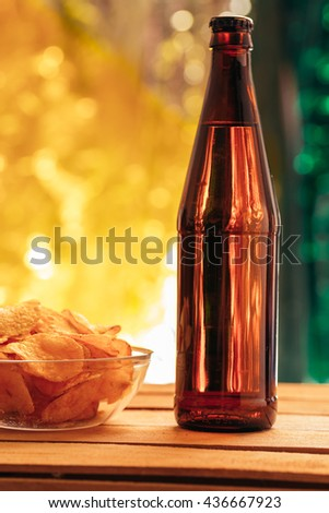 brown beer bottle with a bowl of chips on a blurred background. - stock photo