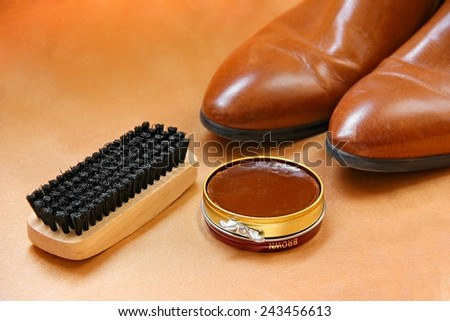 Brown boots with shoe polish and brush shoe care background.  - stock photo
