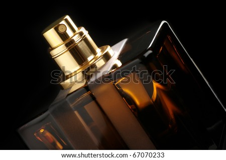 Brown bottle of perfume close-up on black background. - stock photo