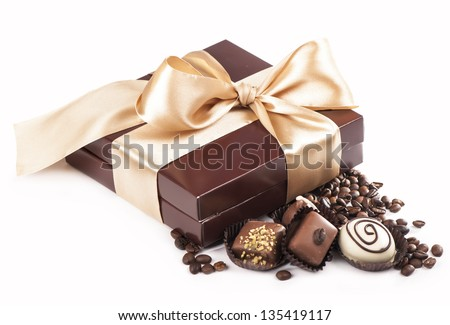 brown box with candies and golden tape, coffee grains - stock photo