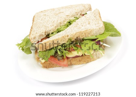 Brown bread sandwich with fresh tomato and lettuce on a white plate with a plain background - stock photo