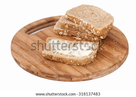 Brown bread with seeds coated with butter. - stock photo