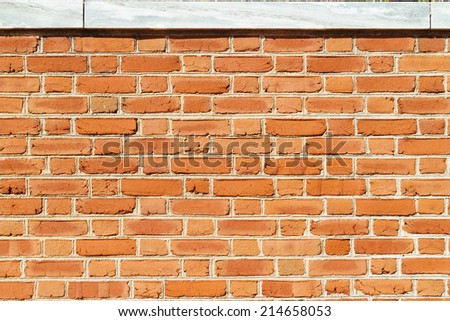 Brown brick wall texture/background. Stone on top. - stock photo