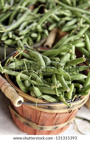 Brown bushel baskets filled with fresh green beans at local farmers market - stock photo