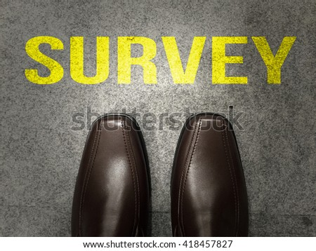 Brown business shoes on floor with text:Survey - stock photo