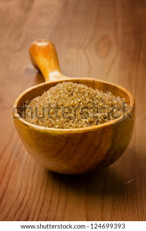Brown cane sugar in a wooden spoon on wood background - stock photo