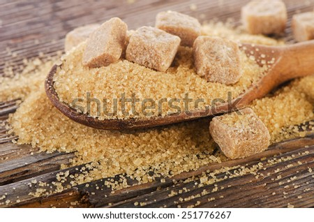 Brown cane sugar in a wooden spoon. Selective focus - stock photo