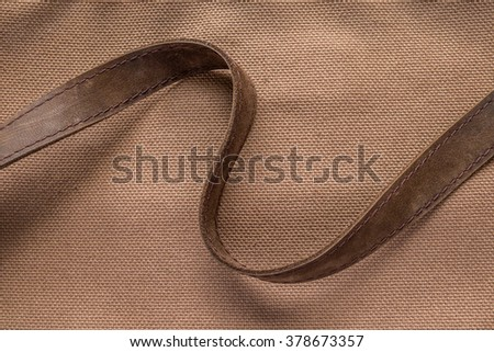 Brown canvas and brown leather ribbon - stock photo