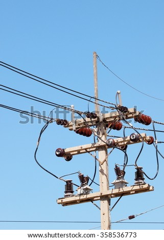 brown ceramic electric insulator dishes or cups on the top of electric pylon, pole connect high voltage electric wires with the system structure and isolate power from the cables, blue sky background  - stock photo