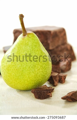 Brown chocolate chunk block and fresh pear. This is perfect harmony of tasting flavor chocolate and pear for cake, muffin, ice cream, fondue, pie, cookies and your favorite desserts. - stock photo