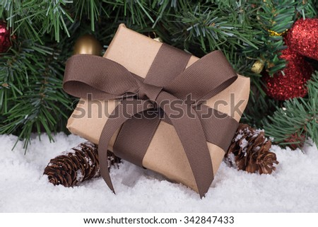Brown Christmas present on snow with a holiday tree in background - stock photo