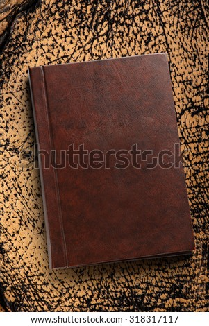 Brown closed book on the leather background  - stock photo
