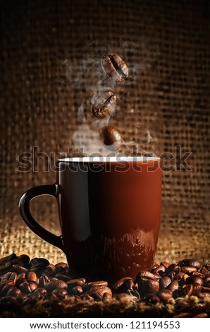 brown cup of coffee with coffee beans - stock photo