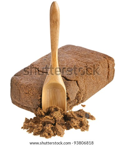 brown dark sugar block with wooden spoon over white background - stock photo