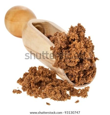 brown dark sugar with wooden scoop over white background. - stock photo