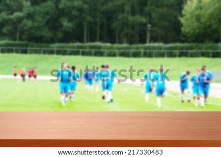 brown desk of sport and men in blue  - stock photo