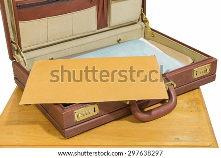 brown envelope in opened old vintage brown briefcase on wood table isolated - stock photo