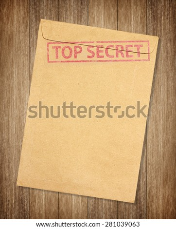 Brown envelope with top secret stamp isolated on on wood background - stock photo