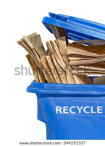 "Brown flattened corrugated boxes in blue plastic recycling bin. Open lid. White letters of the word ""RECYCLE"" on side of container. Isolated on a white background. Vertical composition.   - stock photo"