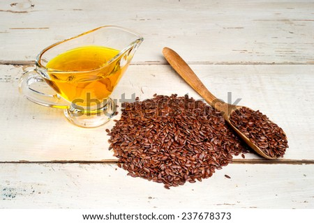 brown flax seed and linseed oil, on wooden table - stock photo